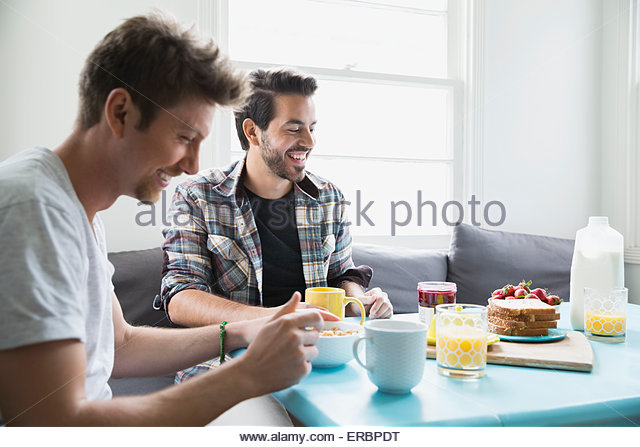 Homosexual couple eating breakfast at table - Stock Image