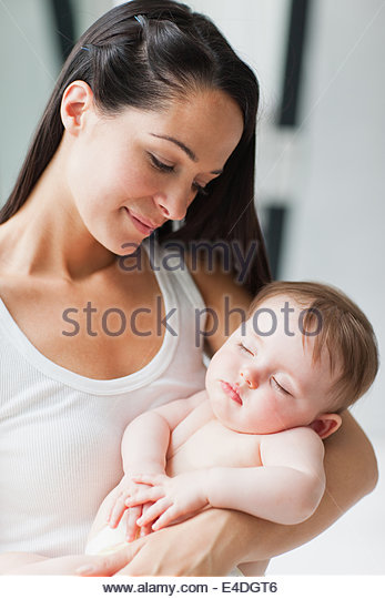 Close up of mother holding sleeping baby - Stock Image