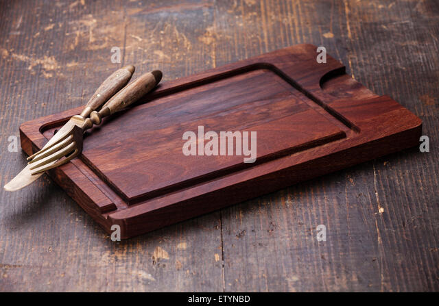 Chopping cutting board with fork and knife on dark wooden background - Stock Image