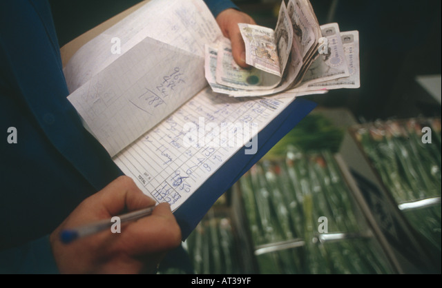 Money changing hands at New Covent Garden Market is the largest wholesale market in UK - Stock Image