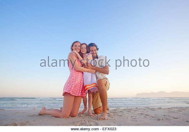 Happy couple kneeling, hugging daughter, on sunny beach - Stock Image