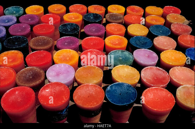 Large handmade wax candles of many colors wait for their wicks to be inserted before being sold at an arts-and-crafts - Stock-Bilder