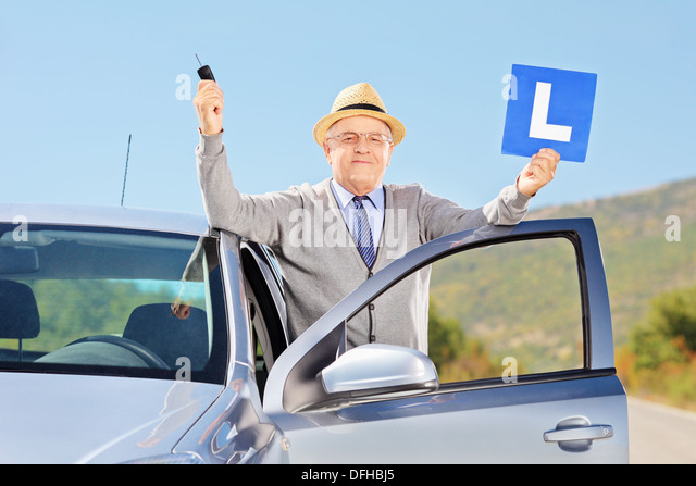 Smiling senior man posing next to his car holding a L sign and car key after having his driver's license - Stock Image