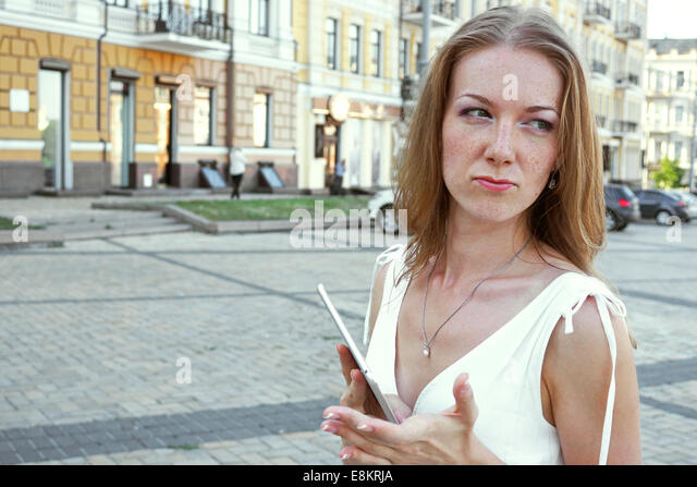 Young angry woman staying outdoor with tablet - Stock Image