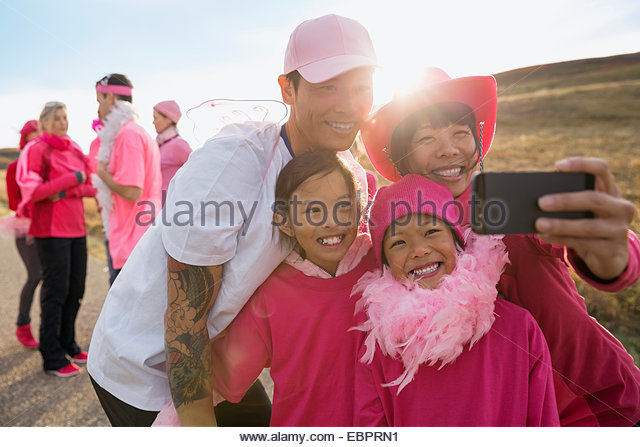 Family in pink taking selfie at charity race - Stock Image