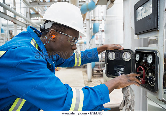 Worker checking gauges at gas plant - Stock Image