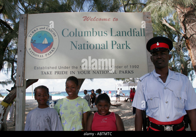 Grand Turk Cockburn Town Columbus Landfall National Park Governor's Beach sign Black children police - Stock Image