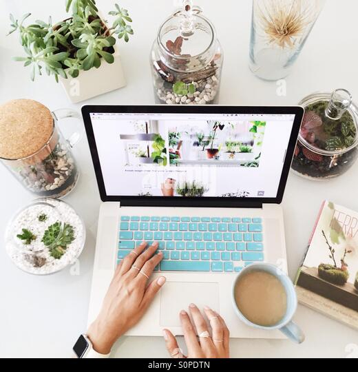 Working on the Mac with a cup of coffee surrounded by terrariums with succulents and other living plants - Stock Image