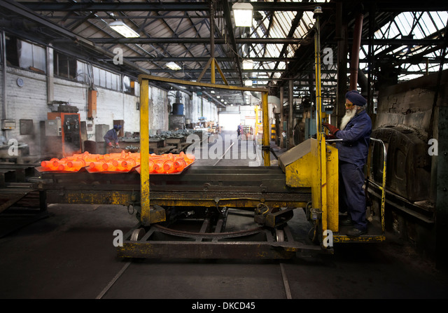 Red hot drive shafts on manipulator ready to unload - Stock Image