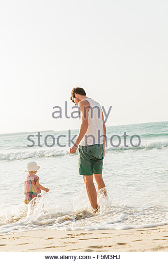 United Arab Emirates, Dubai, Man with son (2-3) on beach - Stock Image
