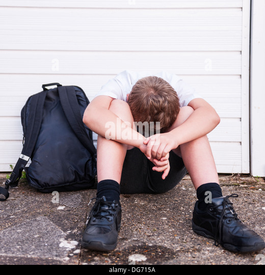A boy of 10 looking sad and depressed in his school uniform showing the effects of bullying in the Uk - Stock Image