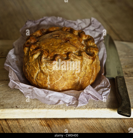 Baked pork pie on wooden board - Stock Image