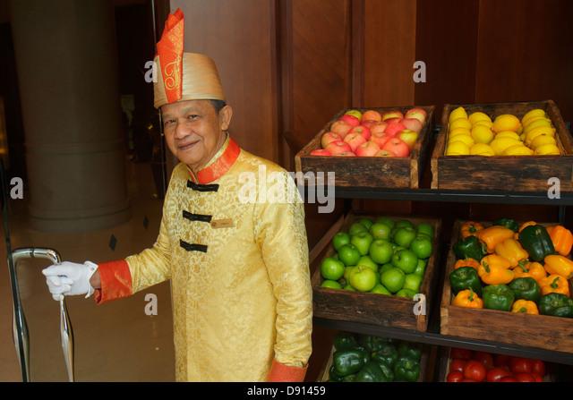 Singapore Fairmont Singapore hotel lobby doorman uniform Asian man employee produce fruit for sale - Stock Image