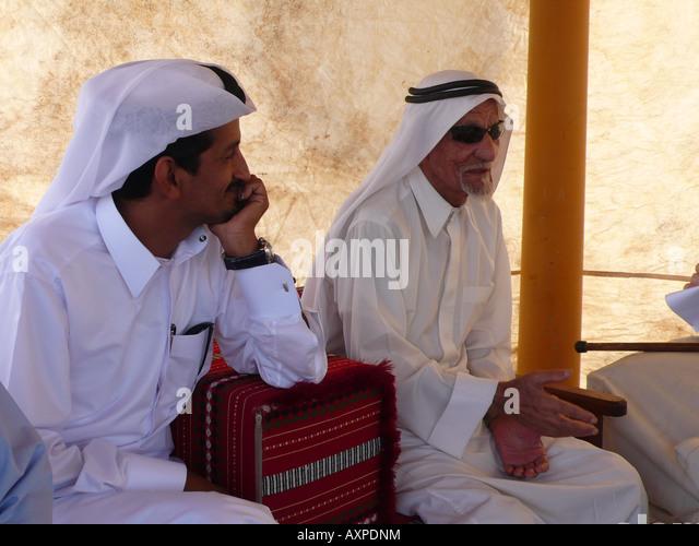 Qatari men in traditional dress at Doha marina - Stock Image