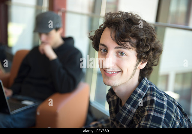 Student with brown curly hair, portrait - Stock Image