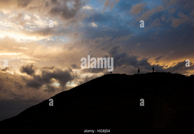 Dramatic silhouette of 3 mountain climbers on the top of a mountain with dramatic cloudy sunset sky. - Stock-Bilder
