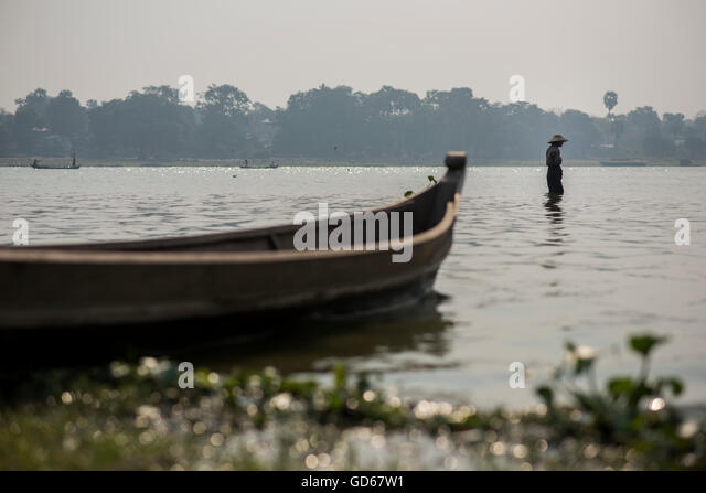 A fisherman fishing in front of his boat at the Taungthaman Lake, Amarapura, Myanmar. - Stock-Bilder