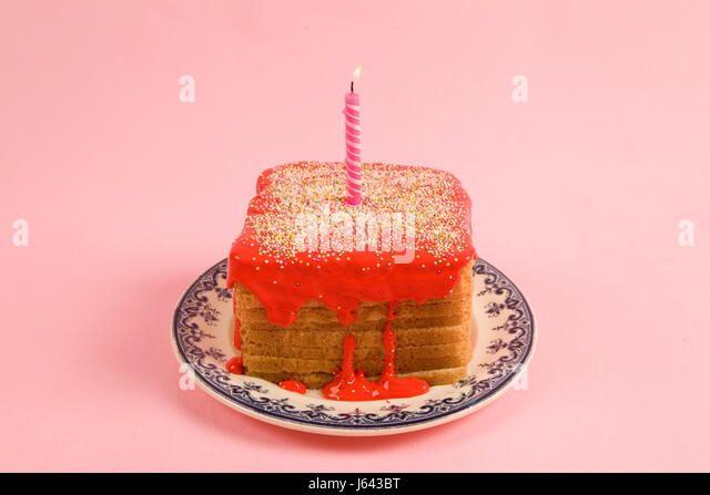 a quirky icing birthday bread covered with sprinkles and red coulis on pink background - Stock Image