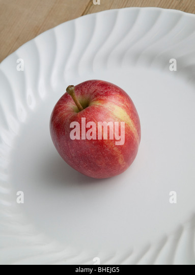 RED EATING APPLE ON WHITE PLATE ON WOODEN TABLE - Stock Image