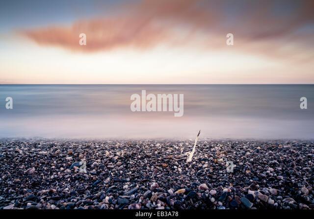 Italia, Sicily, Province of Messina, Messina, Pebble beach and calm sea in evening - Stock Image