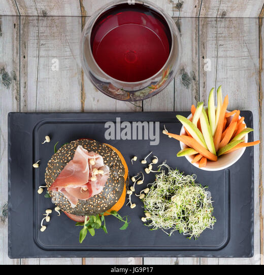 Healthy burger with hamon, tomatoes, micro greens and black wholegrain buns, vegetable sticks and red wine on black - Stock Image