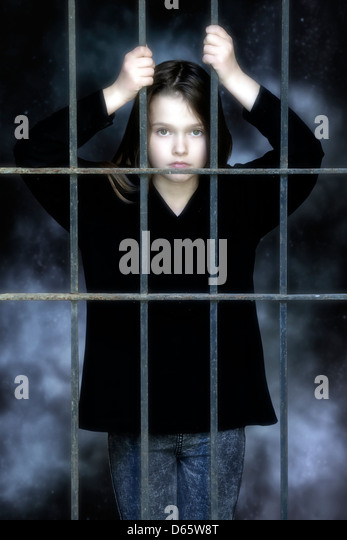 a girl imprisioned behind a grate - Stock Image