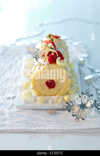 Snow Yule Log with Red Fruits - Stock Image