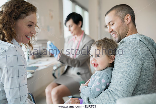 Parents holding baby girl while pediatrician prepares vaccination - Stock Image