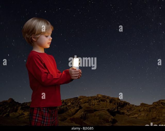 boy with energy saving light bulb - Stock Image