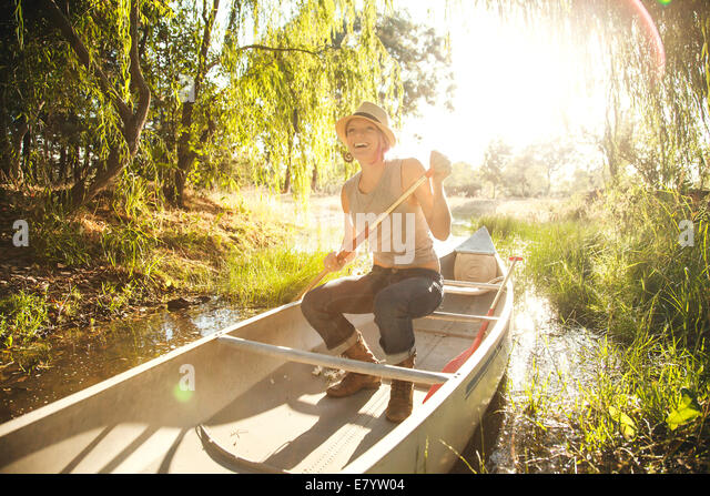 Smiling woman in canoe - Stock Image
