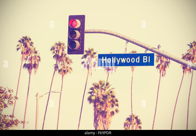 Vintage retro toned Hollywood boulevard sign and traffic lights with palm trees in the background, Los Angeles, - Stock-Bilder