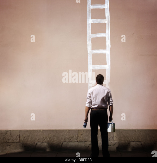 man with painted ladder on wall - Stock-Bilder