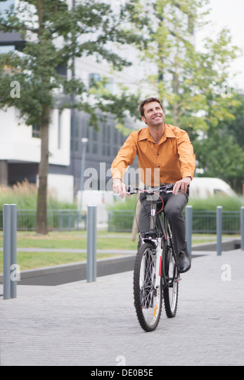 Man in business attire riding bicycle - Stock Image