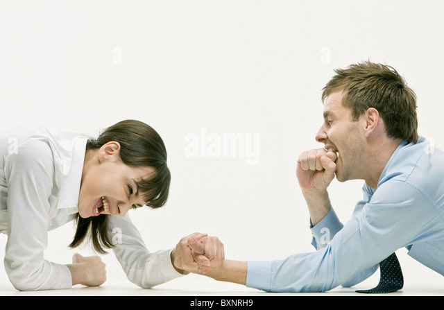 Businessman and woman arm wrestling over table - Stock Image