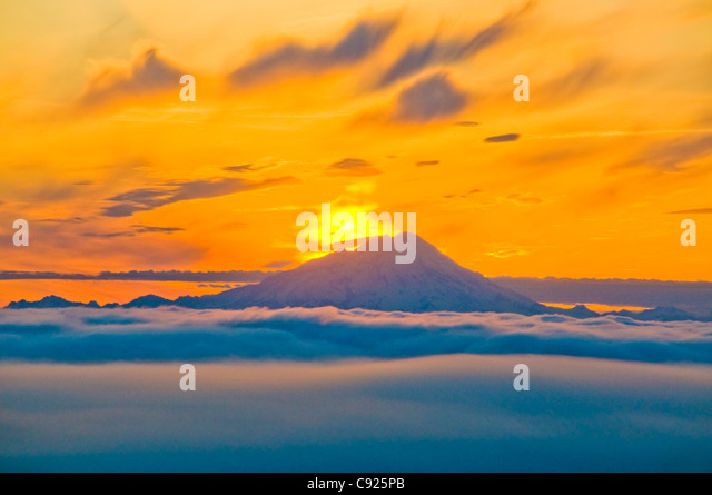 Colorful sunset behind Mt. Redoubt and a low cloud layer as seen from Kenai Peninsula, Southcentral Alaska, Summer - Stock Image