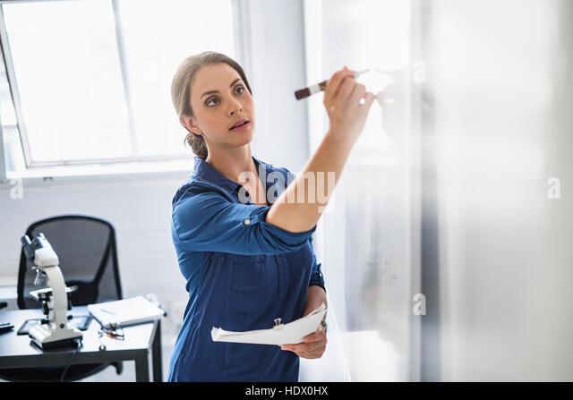 Hispanic professor writing on whiteboard - Stock Image