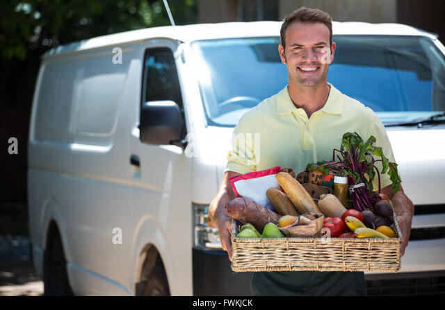 Happy man delivering groceries - Stock Image
