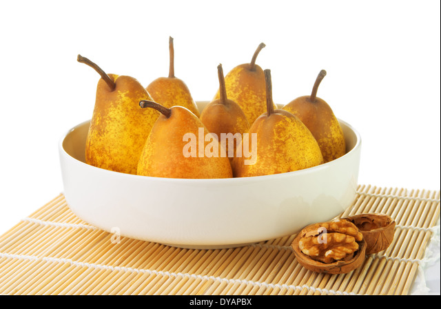 Yellow ripe pears in a white bowl with a walnut - Stock Image