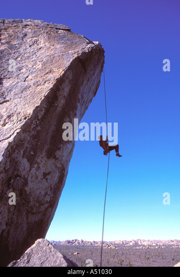 Rock climing man rappeling off of rock with desert landscape in background Joshua Tree California USA - Stock Image