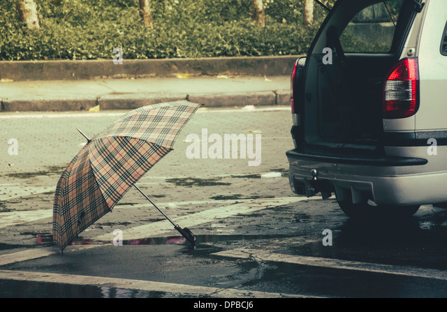 Brazil, Sao Paulo, Umbrella and car on the street - Stock Image