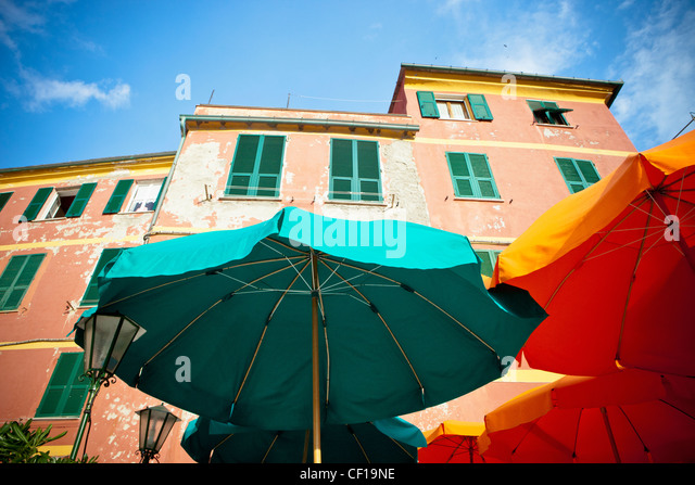Green And Yellow Patio Umbrellas Beside A Building; Vernazza Liguria Italy - Stock Image