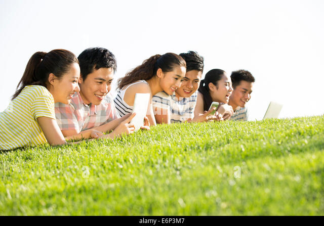 Cheerful young adults lying down on grass playing together - Stock Image