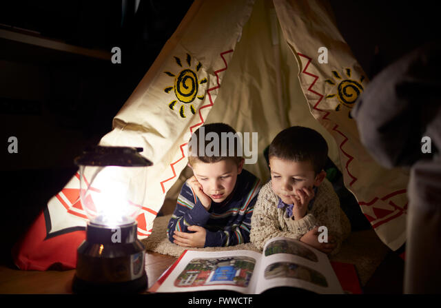 Two Young Boys Reading Inside Tent Set Up Indoors - Stock Image
