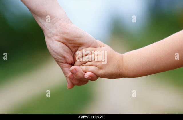 Hands of mother and child. Holding hands. Shallow depth of field. - Stock Image