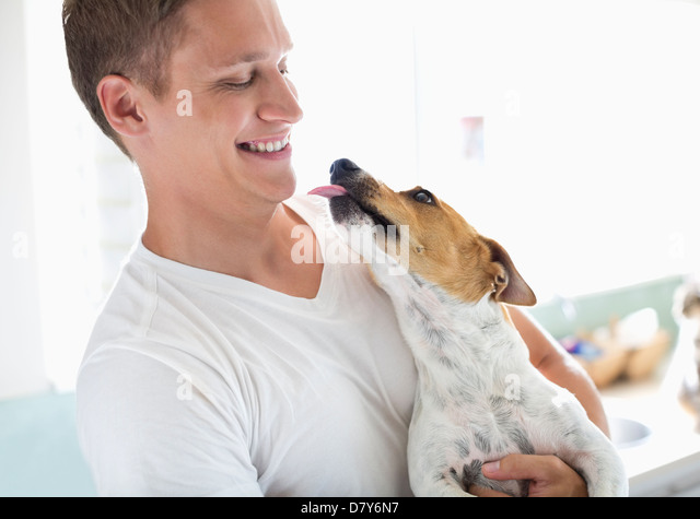 Smiling man holding dog - Stock Image