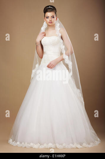Wedding. Beautiful Graceful Bride in White Long Dress and Viel - Stock Image