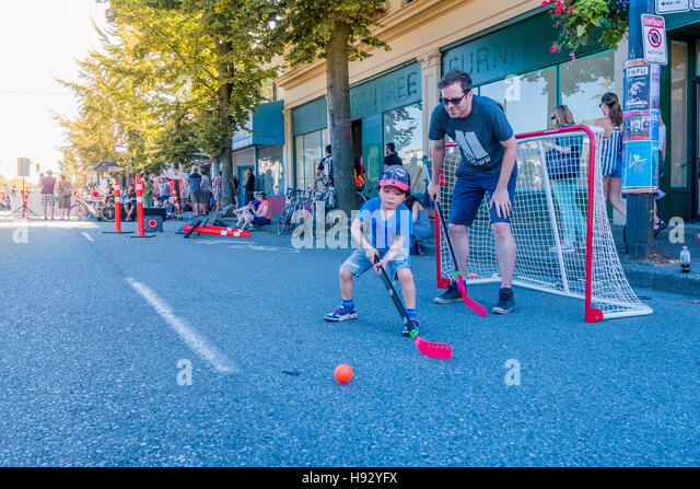 Father and son playing road hockey, Vancouver, British Columbia, Canada, - Stock Image