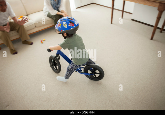 Boy learning to ride bicycle, high angle - Stock Image