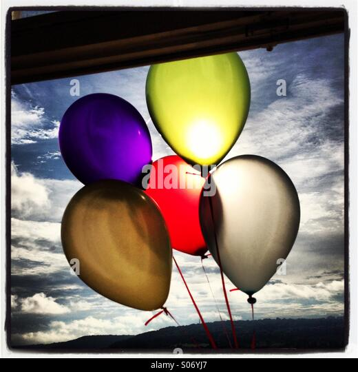 Brightly coloured balloons in front of the sun outside a window against a blue sky with white fluffy clouds. - Stock Image
