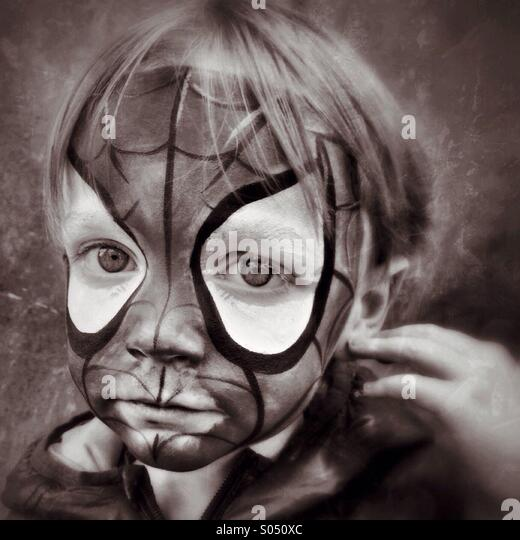 Sad Spidey. Boy unhappy in Spider-Man face makeup - Stock Image